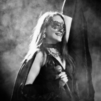 Ann wearing batwings and a Halloween mask, smiling and raising her left hand while holding her mic in her right hand. Black and white.