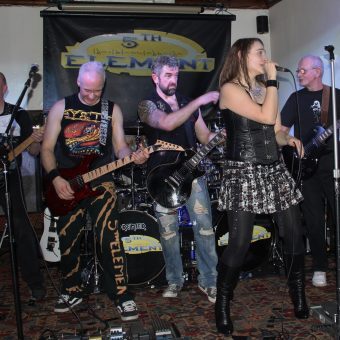 The band performing on stage, complete with Rocker.