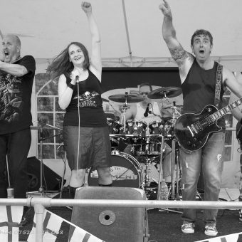 Richard, Ann, Alan and Neil all jumping up and down together on stage. Black and white.