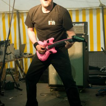 Richard playing a pink inflatable guitar on stage.