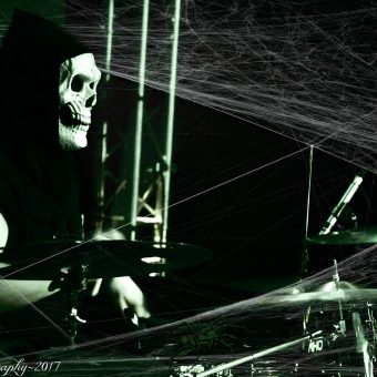 Aaron playing drums, wearing a grim reaper mask, with cobwebs on his drum kit, Black and white.