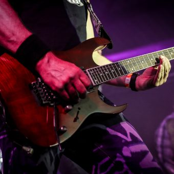 Close up of Neil playing his red Ibanez guitar.