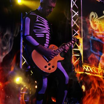 Alan playing guitar, wearing a skeleton costume.