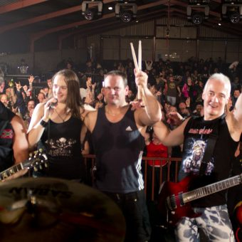The band pose for a group shot in front of the crowd.