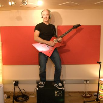 Neil standing on top of his amp at the studio, colour.