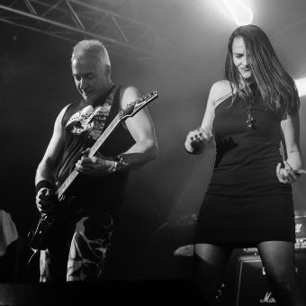 Neil playing guitar while Ann plays air guitar next to him. Black and white.