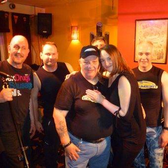 Richard, Phil, Harry Stubbs, Ann, Alan and Neil posing for a group shot on stage at Wangies, Eccles.