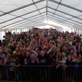 The crowd at Rock The Lakes music festival, cheering and waving their arms.