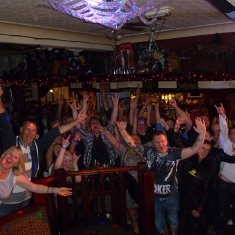 The crowd at the Bath, Morecambe, cheering and waving their arms.