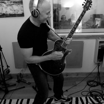 Neil posing with his guitar at the studio, black and white.