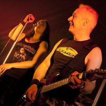 Ann singing, Neil playing guitar and smiling.