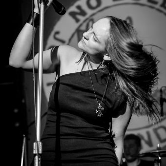 Ann holding her mic in its stand and whipping her hair, black and white.