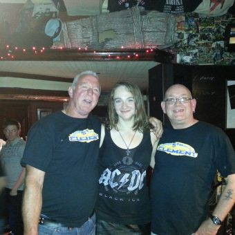 Ann standing between two men (Russell and Mick) wearing 5th Element t-shirts on stage at the Bath, Morecambe.