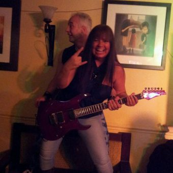 Neil standing behind a woman (Sharon) as she plays his red Ibanez guitar for him.