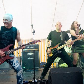 Neil, Richard and Ann performing on stage. Neil is laughing.