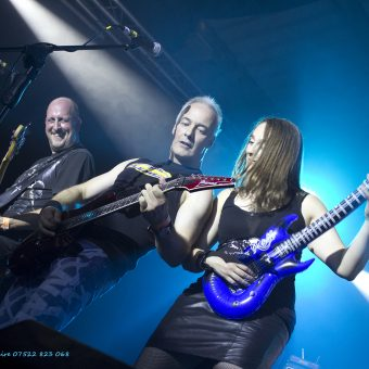 Richard, Neil and Ann throwing shapes on stage. Ann playing an inflatable guitar.