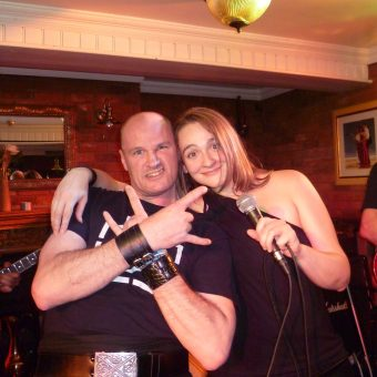 A man (Colin) giving the sign of the horns with his arms crossed, posing with Ann, who's holding her microphone.