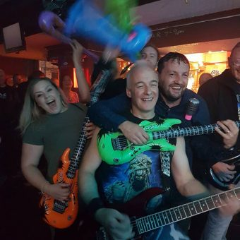 Neil playing a real guitar, in the crowd with a girl (Alex) and a man (Paul), both playing inflatable, coloured guitars and smiling.