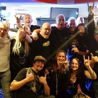 The crowd at the Bull, Morecambe, cheering and waving their arms. Ann in the middle with a glass of white wine, giving the rock horns salute.