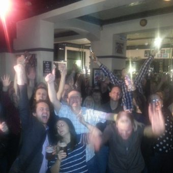 The crowd at the Pub, Lancaster, cheering and waving their arms.