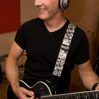 Neil playing guitar and smiling at the studio.