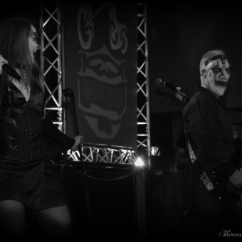 Ann and Neil performing on stage. Neil is wearing a scary Halloween mask.