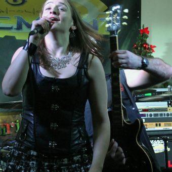 Ann singing, Alan throwing shapes on his guitar.