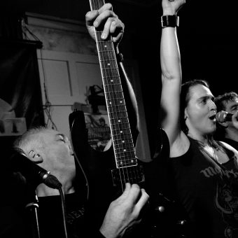 Neil raising his guitar as Ann sings and raises her first. Black and white.