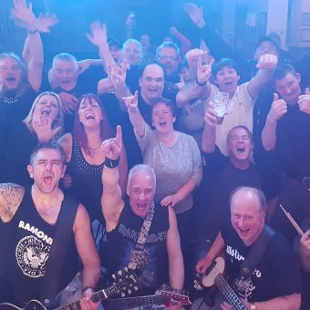 The crowd at Saith Seren, Wrexham, cheering and raising their arms. Alan, Neil, Pete and Aaron all at the front.