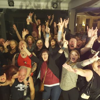 The crowd at Saith Seren, Wrexham, cheering and waving their arms. Neil at the front getting a kiss on the cheeky from Kate.
