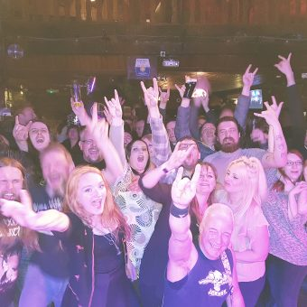 The crowd at Bootleggers, Kendal, cheering and waving their arms (Neil in the middle).
