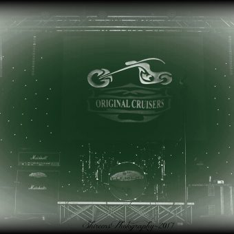 The stage, with the Original Cruisers' backdrop hung above the drum kit. Black and white with a hazy effect.