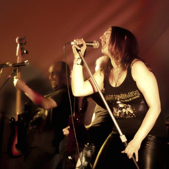 Ann belting on the mic while Richard throws shapes on his bass.