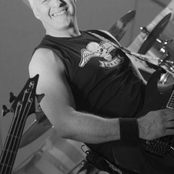 Neil smiling and playing guitar on stage. Black and white.
