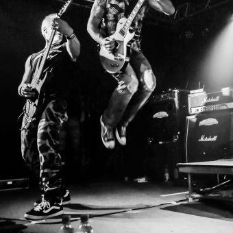 Neil playing guitar and looking over his shoulder in surprise as Alan, playing guitar, jumps high into the air. Black and white.