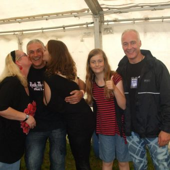 2 women kissing a man (Mike) on the cheek, a young girl (Emma) giving the thumbs up and Neil smiling at the camera.