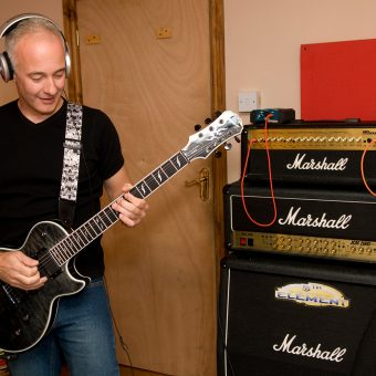 Neil playing guitar in the studio, colour.