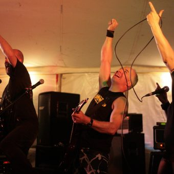 The band performing with their arms raised.