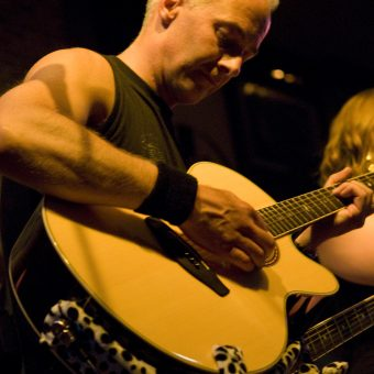 Neil playing acoustic guitar.