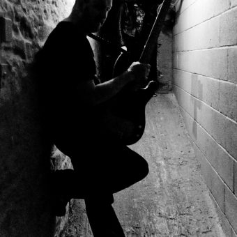 Richard standing in a corridor at the studio, silhouette.