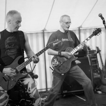 Neil and Rocker performing on stage. Black and white.