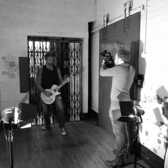 Alan playing guitar in a corridor while cameraman Sam films him. Black and white.