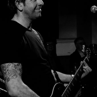 Alan playing guitar and smiling, black and white.