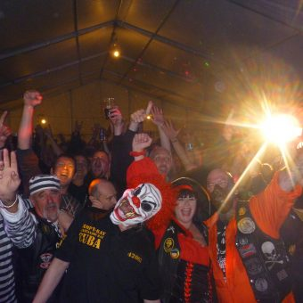 The crowd at Autumn NABDness, cheering and waving their arms. The front row is in fancy dress. Left to right: 2 convicts in striped prisoners outfits, a scary clown, a female pirate, Hannibal Lecter and a girl in a cowboy hat.