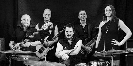The band, posing against a black screen.