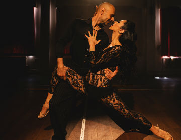 A photo of dancer Richard Manuel holding fellow dancer Paula Duarte in a tango pose. Richard is wearing all black, Paula is wearing a black lace body stocking. Both are smiling at each other.