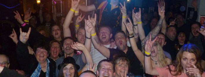 The crowd at the Fox and Goose, Southport, cheering and waving their arms.