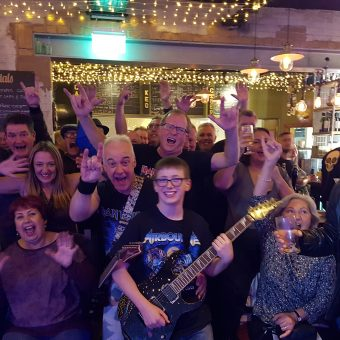 The crowd at Remedy Bar and Brewhouse, Stockport, cheering and waving their arms.