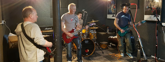 Pete, Neil, Aaron and Alan playing songs in a rehearsal room.
