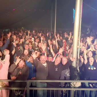 The crowd at the Farmyard Party 2019, cheering and waving their arms.